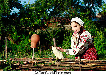 Russian girl in ethnic costume at wattle fence with white kitten