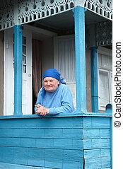 Russian grandmother on the veranda in village house