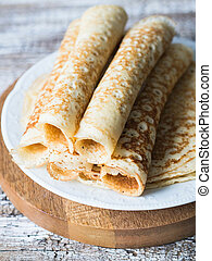 Russian homemade yeast crepes rolled into a tube on white plate. Traditional wheat pancakes for Shrovetide.