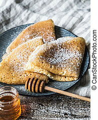 Russian homemade yeast pancakes on blue plate, sprinkled with powdered sugar, wood honey spoon on wooden table. Traditional wheat pancakes for Shrovetide.