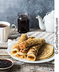 Russian homemade yeast pancakes rolled into a tube on white plate, jam and tea in the mug on wooden table. Traditional wheat pancakes for Shrovetide.