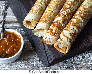 Russian homemade yeast pancakes rolled into a tube on wood board, apricot jam in bowl on table. Traditional wheat pancakes for Shrovetide.