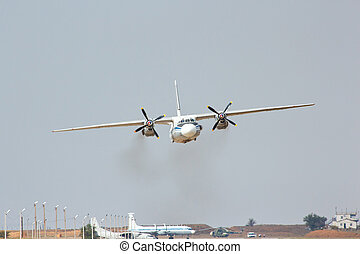 Russian military transport aircraft AN-26 is landing on the airfield