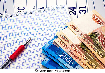 Russian money and a Notepad, a red pen and Russian banknotes, a clean sheet and a red pen