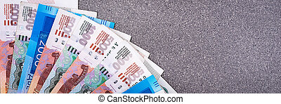 Russian money, one thousand rubles, two thousand rubles, five thousand rubles, background image, bills arranged in a fan on a gray background.
