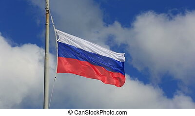 Russian national flag waving on flagpole in blue sky. Russia