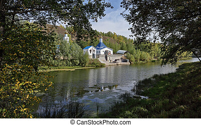 Orthodox Church on the shore of a pond in autumn