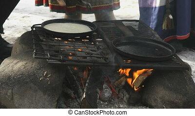 Russian pancakes on frying pan on bonfire