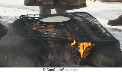 Russian pancakes on frying pan on bonfire