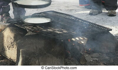 Russian pancakes on frying pan on bonfire - Process of...
