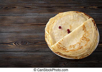 pancakes with berries on a dark wooden background, top view