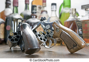 Two weapons with only one bullet each. At the bottom a few bottles of whiskey. Concept of challenge and test of courage.