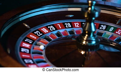 Russian roulette wheel is spinning at a casino and the small white ball is lying in a slot.