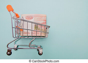 russian rubles in shopping cart on blue background with copy space