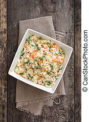 Russian salad in bowl on a rustic wooden table