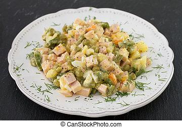 russian salad on plate on dark background