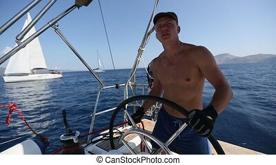 Russian skipper at the helm controls of a sailing yacht...