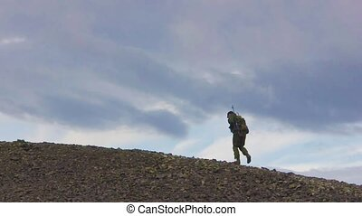 Russian soldier with a rifle. Steps against mountains. -...