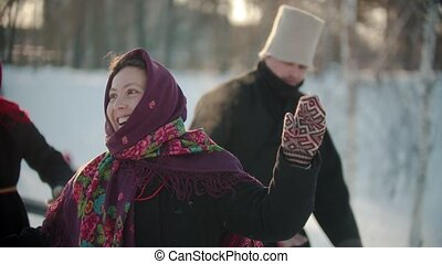 Russian traditions - a woman in traditional clothes is dancing merrily to the music of the accordion