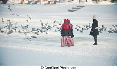 Russian traditions - people in beautiful clothes are chasing pigeons on a frozen pond