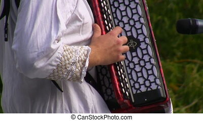 Russian Eastern European folk musician dressed in traditional clothes plays the bayan, Russian accordion on outdoor stage