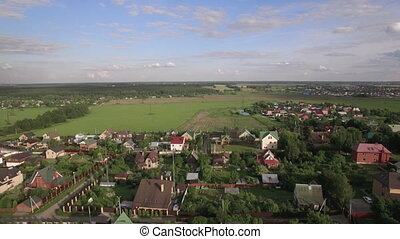 Flying over the cottages and houses in the village located among green fields and forests. Lukino, Russia