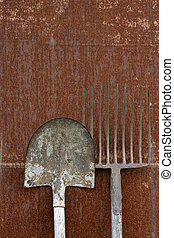 rust and tools - a rusty wall, a hay-fork and a blade