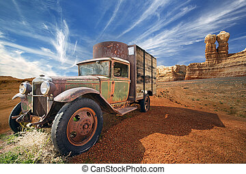 rusted abandoned truck in a rocky desert landscape