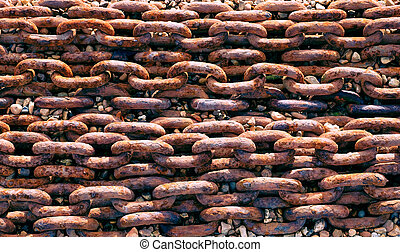 rusted chain - lines of rusted large metal chain on a stony...