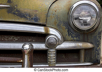 rusted chrome front bumper, headlight and grill of old junk car with peeling paint and rust