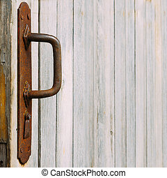 Rusted handle and old wooden wall. Texture. Background.