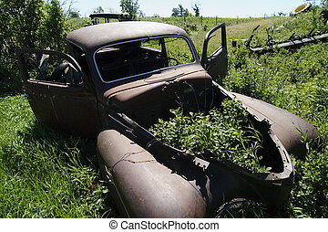 An old rusted out car on the prairie landscape