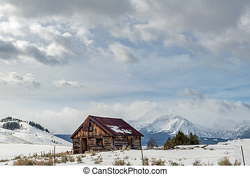 Rusted roofed log cabin in the Idaho wilderness winter with clouds in the sky