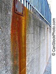Rust heavily stains a concrete wall with an iron fence on top of it.