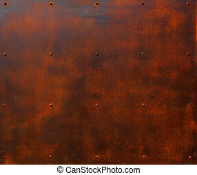 Brown and red rusted steel plate with rows of screw heads