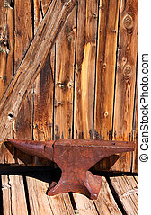 Rustic Anvil - Old rustic Anvil with wooden wall background