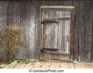 isolated rustic door in historic building, with large iron hinges