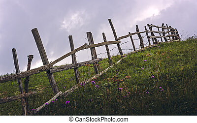 Rustic fence across a meadow - Rustic wooden fence across a...