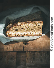 Rustic French rye bread loaf on wooden board, copy space