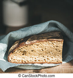 Rustic French rye bread loaf on wooden board, square crop