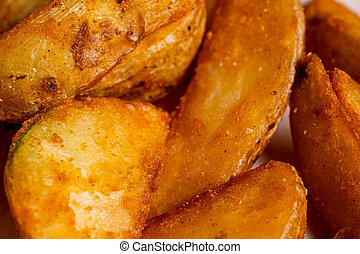 Rustic fried potato in close-up on a paper background.