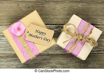 Rustic gift boxes with Happy Mothers Day tag on a wood background