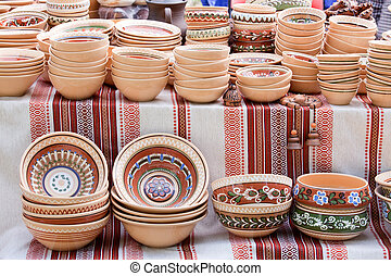 Rustic handmade ceramic clay brown pots souvenirs decorated by traditional ornament, pattern on embroidered Ukrainian towel at street handicraft market