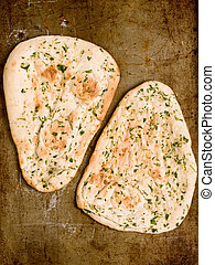 rustic indian garlic and parsley naan bread - close up of...