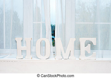 Rustic interior decor. Word Home on windowsill.