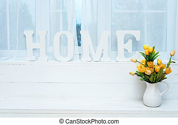 Rustic interior decor. Word Home on windowsill with white jug full of yellow tulips.