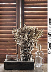 Rustic kitchen utensil against wooden shutters: bunch of dry flowers and glass bottles.