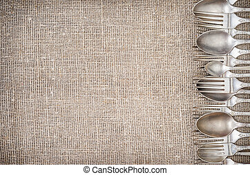 Rustic linen background with vintage silver cutlery