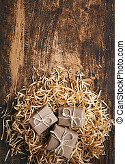 Rustic little gift boxes on wooden textured background with space for text. Top view