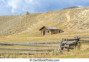Rustic Log cabin on the plane with a fence